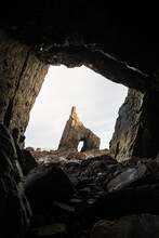 From Stony Rough Cave Scenery Of Sharp Severe Rock With Hole Located On Stony Spacious Terrain In Daylight