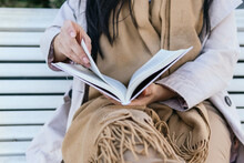 Cropped Unrecognizable Female Reading Book Sitting In Bench