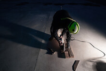 From Above Full Body Of Unrecognizable Male Welder In Protective Helmet And Goggles Cutting Iron Details With Chop Saw During Work At Industrial Factory At Night