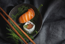 Tasty Fresh Assorted Sushi Served On Green Plant Twigs On Black Plate With Soy Sauce On Marble Table Near Chopsticks