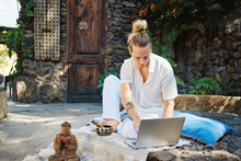 Young Male Surfing Internet On Netbook While Sitting Against Buddha Statuette And Bowl Gong In Patio