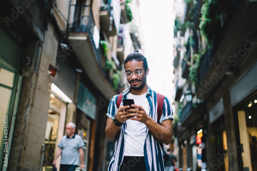 Foto Positive young ethnic man browsing cellphone while walking on street