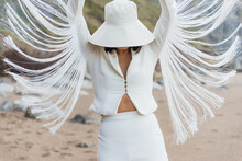 Unrecognizable Slim Female Model In Elegant White Hat And Suit With Straps Looking Like Wings Raising Arms While Standing On Sandy Beach