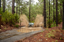Modern Off Roader Car Driving Through Muddy Puddle On Rural Dirt Road In Lush Green Woodland In Daylight