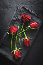 Top View Composition Of Bright Red Blooming Rose Buds Scattered On Black Surface With Cloth