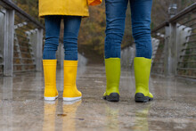 Back View Of Crop Anonymous Children In Jeans And Colorful Gumshoes Standing On Wet Bridge Under Rain In Autumn Park