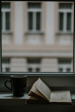 Textbook With Circles From Beverage On Page Near Mug Against Window And Building In Evening