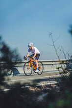 Full Body Of Young Sportsman In Activewear And Helmet Riding Bicycle On Asphalt Road On Sunny Day