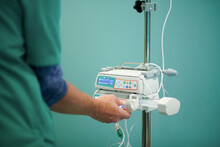 Side View Of Crop Anonymous Doctor In Medical Uniform Controlling IV On Modern Infusion Pump In Operating Room