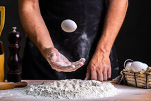 Faceless Male Baker In Black Apron Tossing Raw Egg Above Pile Of Flour Making Bread