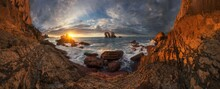 Amazing Panoramic Scenery Of Rough Rocky Formations Washed By Foamy Sea Waves Under Cloudy Sunset Sky On Playa De La Arnia In Spain
