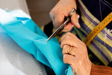 High Angle Of Crop Anonymous Elderly Dressmaker Cutting Piece Of Cloth While Working In Workshop
