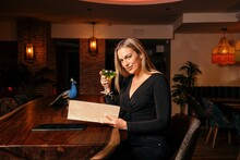 Side View Of Positive Young Female Customer With Long Blond Hair In Stylish Clothes Smiling And Reading Menu While Enjoying Cocktail In Modern Bar