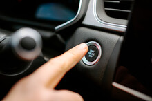 Closeup Of Crop Anonymous Male Pressing Start Engine Stop Button While Sitting In Modern Car Before Driving