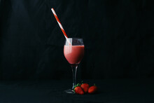 Flow Of Yummy Beverage Pouring Into Transparent Glass With Striped Straw Near Juicy Strawberries On Black Background