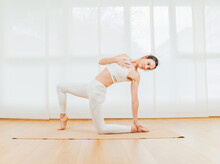 Side View Full Body Of Focused Female Doing Backbend With Crescent Lunge On Knee  And Touching Foot