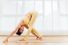 Full Body Side View Of Focused Female Bending Forward With Head Upside Down Practicing Yoga