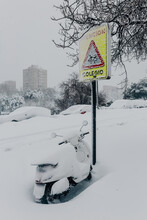 Contemporary Motorbike Parked Near Road Sign And Covered With Thick Layer Of Snow In City Suburb On Freezing Winter Day