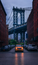 View Of Brooklyn Bridge Seen From Urban Street With Driving Car With Glowing Headlights In Gloomy Autumn Day In New York City