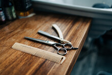 From Above Scissor And Comb Near Straight Razor With Sharp Metal Blades On Wooden Table In Hairdressing Salon