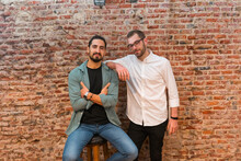 Smiling Male Baristas Looking At Camera On Background Of Shabby Brick Wall In Cafe In Loft Style