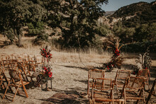 Empty Area With Wicker Chairs And Arch With Flowers Prepared For Wedding Ceremony In Garden On Sunny Day In Summer