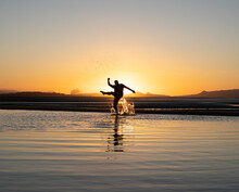 Silhouette Of Anonymous Male Traveler Kicking Water Of Rippling Sea Against Cloudless Sunset Sky During Summer Holidays In Australia