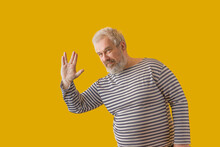 """A Man With A Gray Beard, Gray Hair, Wearing A Sailor's Shirt, Shows The """"vulcan Salute"""" Sign. On A Yellow Isolated Background."""
