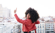 Back View Of African American Female With Curly Hair In Stylish Outfit Standing On Balcony And Looking At City Buildings