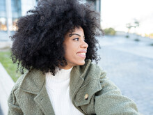 Trendy Young Black Female Millennial With Afro Hair In Stylish Warm Clothes Resting On Street And Looking Away Pensively Near Modern Building With Glass Walls