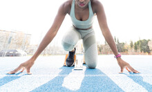 From Below Of African American Female Runner In Starting Blocks Sitting In Crouch Position While Getting Ready For Sprint At Stadium During Workout