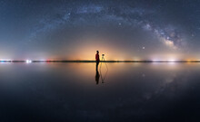 Side View Of Anonymous Photographer With Photo Camera Standing Under Night Sky With Glowing Stars In Long Exposure