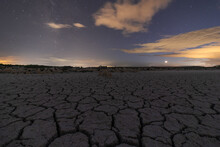 Picturesque Panoramic View Of Cracked Desert Terrain Under Starry Night Sky With Milky Way