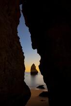 Through Rocky Cave Of Picturesque Sandy Beach Of Ocean Against Sunset Sky In Praia Do Camilo In Algarve, Portugal