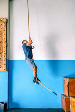 Side View Of Disabled Male Athlete In Sports Clothes Climbing Workout Rope Near Bright Wall In Gym