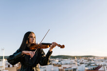 Young Beautiful Female Musician In Stylish Mini Dress Holding Acoustic Violin And Standing On Rooftop In Residential Suburb And Looking Away On Sunny Evening