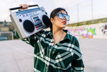 Young Trendy Female In Sunglasses Reflecting Cloudy Sky Listening To Song From Old Tape Recorder Against Graffiti Wall In Sunlight