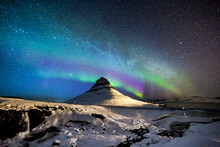 Amazing View Of Aurora Borealis Glowing In Night Sky With Stars Over Mountain Covered With Snow In Winter In Iceland