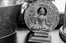 Buddha Figurine On A Background Of Bronze Circles.