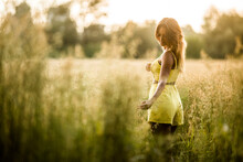 Side View Of Tranquil Female In Yellow Outfit Standing In Field And Touching Grass In Salburua Park In Summer