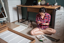 From Above Ethnic Asian Female Sitting On Floor And Screwing Screws In Wooden Board While Assembling New Furniture At Home