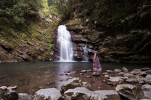 Side View Of Female Tourist Standing On Rock Near Tiemu Falls In Forest In Taiwan