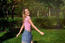 Cheerful Teenage Female Standing In Splashes In Sunny Park