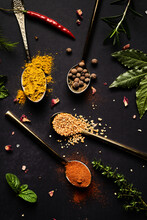 Top View Of Assorted Aromatic Spices In Spoons And Fresh Herbs Arranged On Black Background