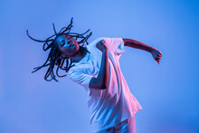 Dynamic African American Teenage Girl Making Movement While Performing Urban Dance In Neon Light Against Blue Background