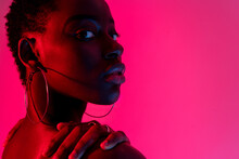 Portrait Of Self Assured Young African American Female Model In Black Top Looking Over The Shoulder While Standing Against Pink Background In Neon Light