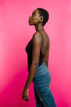 Side View Of Confident Young Fit African American Female Model In Black Top And Jeans Looking Away While Standing Against Pink Background
