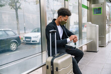 Side View Of Traveling African American Male In Protective Mask Sitting On Bench With Suitcase And Checking Time Of Train Arrival