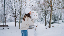 Side View Of Young Cheerful Female With Snowman Head In Park With Leafless Trees In Wintertime
