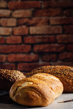 White And Rye Bread With Cereals And Appetizing Crust On Cutting Board Against Brick Wall In Bakehouse